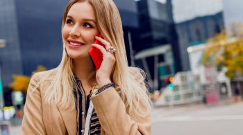 Close up portrait of smiling woman talking by mobile phone. Successful business lady using smartphone. Stylish accessories.  Beige coat. Urban buildings on background.